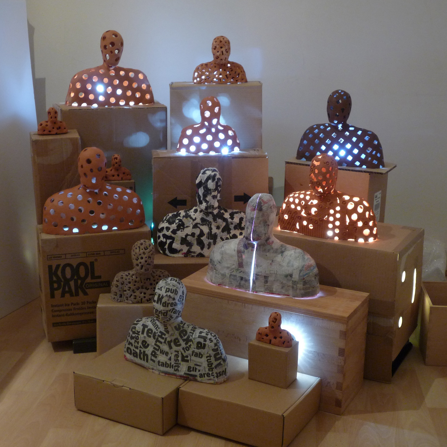 A tableau of 13 or more figures in terra-cotta, plaster and papier mache on stands illuminated by LED lights