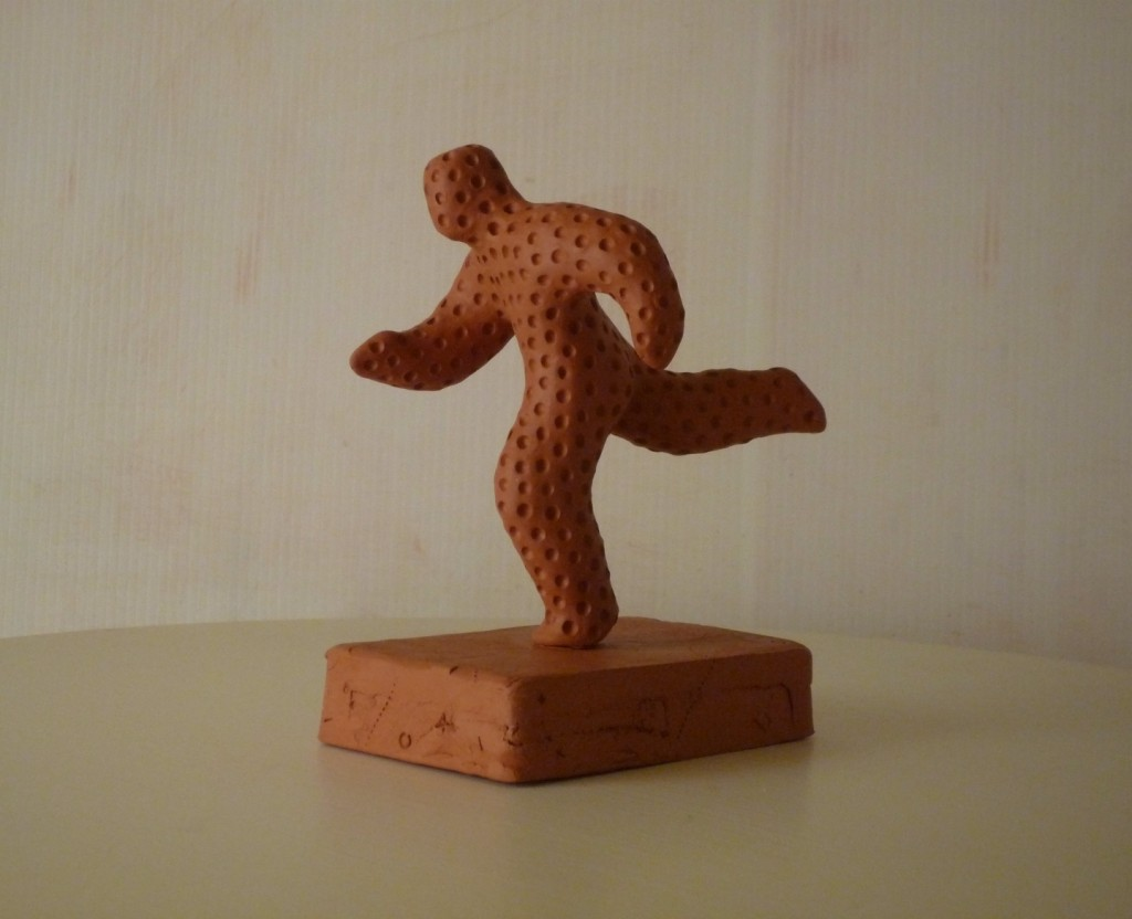Clay figure of a runner mid stride with a dimpled texture overall and on a rectangular base, height about 13cm