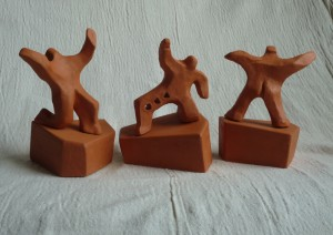 3 male figures assume energetic postures. Terra cotta height 12cm overall.