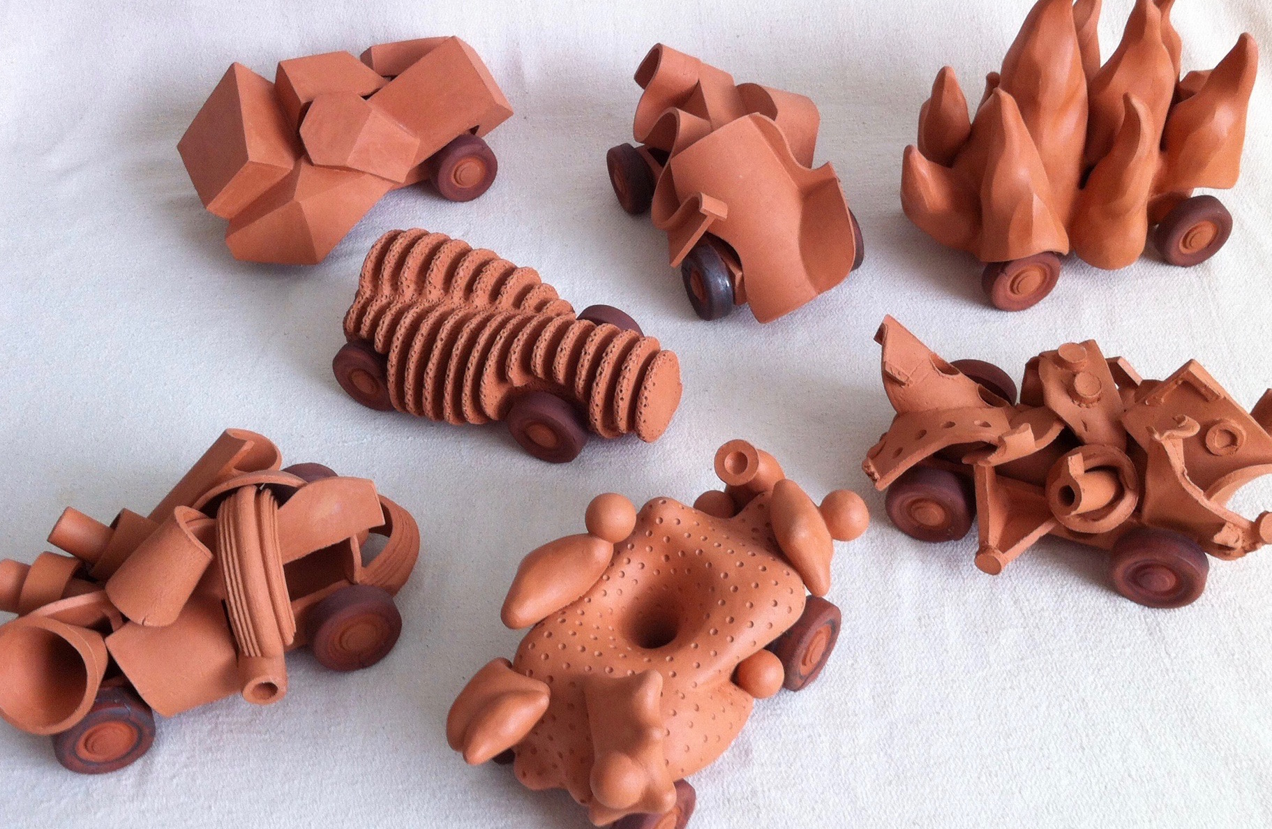 A series of nine 'cars' made of terra-cotta