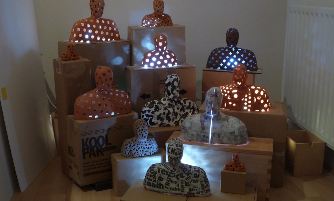 A tableau of 13 or more figures in terra-cotta, plaster and papier mache on stands made of recycled board and mdf illuminated by LED lights